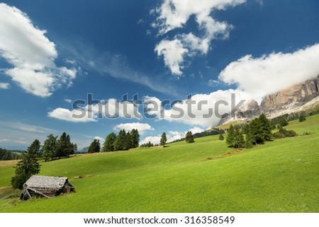 hut in alpine meadow and dolomites in the background - stock photo