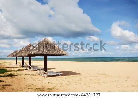 hut umbrella and deck chairs on the sandy beach near the blue sea - Phu Quoc island in vietnam