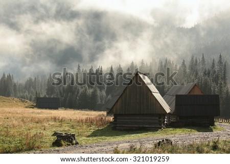 Huts in the valley of the Tatra Mountains on a foggy morning. - stock photo