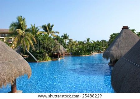 Huts on water in coast of the southern sea, tropical beach with palm trees, Sanya, China - stock photo