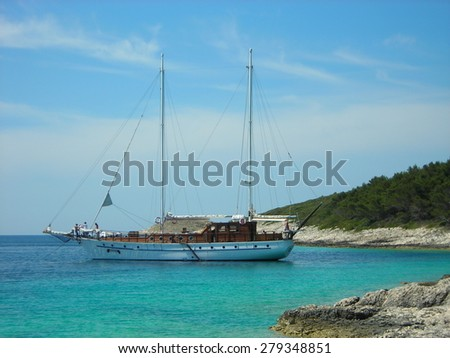 HVAR ISLAND, CROATIA - MAY 31, 2008: Old-fashioned boat in one of the many beautiful bays with turquoise water off the coast of the Croatian island of Hvar, on Adriatic sea, on a clear sunny day.
