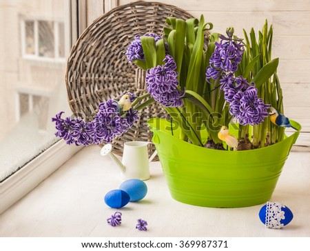 Hyacinths and daffodils on the window next to Easter eggs - stock photo