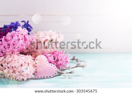 Hyacinths  and  decorative heart in ray of light  on  turquoise painted wooden background against white wall. Selective focus is on flowers. Place for text. - stock photo