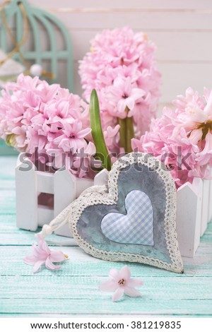 Hyacinths flowers in wooden box and decorative heart on turquoise painted wooden background against white wall. Selective focus.