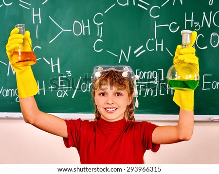 HYappy teen holding flask in chemistry class. - stock photo