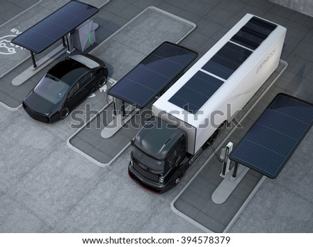 Hybrid electric truck and white electric car in charging station - stock photo