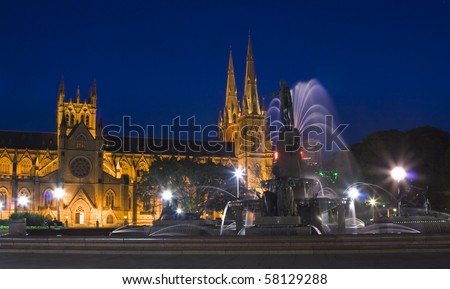 Hyde park Sydney archibald fountain dusk blurred water streams highlighted statue and cathedral with lights and towers - stock photo