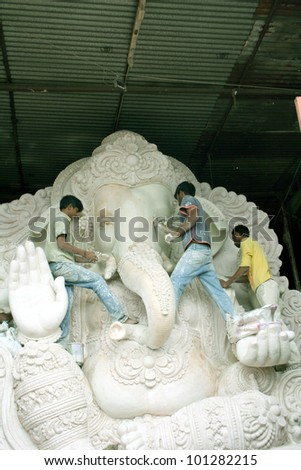 HYDERABAD,AP,INDIA-AUGUST 23:Artists making the ganesha idol for the hindu festival ganesha chathurthi August 23,2011 in Hyderabad,India.Thousands of Idols in different sizes are made every year. - stock photo
