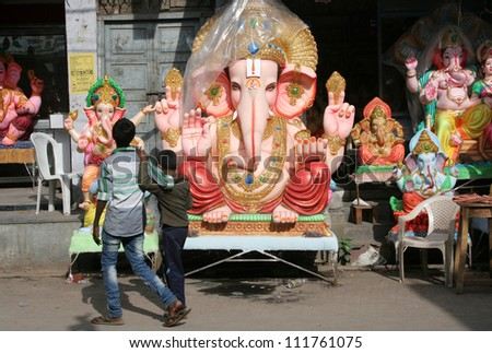 HYDERABAD,AP,INDIA-SEPTEMBER 02:Children looking at  Ganesh idols kept for sale during hindu festival ganesh chathurthi on September 02,2012 in Hyderabad,India.Thousands of idols are made every year. - stock photo