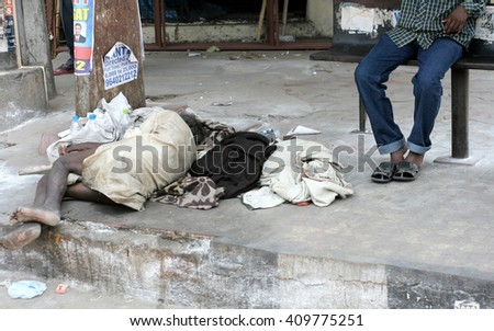 HYDERABAD,INDIA-APRIL 22::Poor Indian senior man sleep in a Bus stop on a busy road on April 22,2016 in Hyderabad,India.