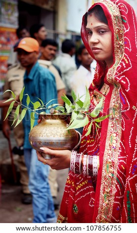 HYDERABAD, INDIA - JULY 15: An unidentified Hindu bride, dressed in traditional outfit, carries a brass pot to a temple for famous Bonalu festival during monsoon on July 15, 2012 at Hyderabad, India. - stock photo