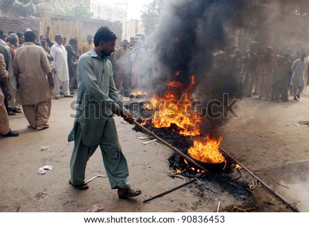 HYDERABAD, PAKISTAN - DEC 14: Angry protesters burn tires during protest demonstration of shopkeepers against standing of sewerage water in bangles and cloths market on Wednesday, December 14, 2011 in Hyderabad, Pakistan.