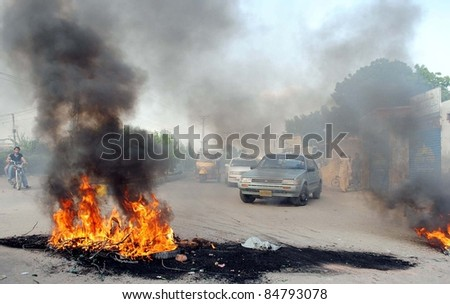 HYDERABAD, PAKISTAN - SEPT 16: Motorists stop due to burning tires which were set ablaze by angry protesters at Wahdat Colony during protest demonstration of Hyderabad against standing rainwater in area September 16, 201, Hyderabad