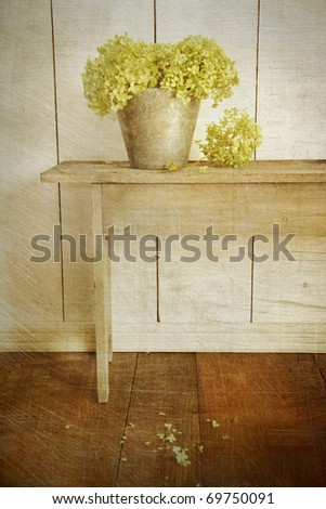 Hydrangea flowers in bucket on rustic bench with age vintage look - stock photo