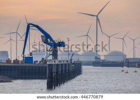 Hydraulic blue Harbor Crane in the port of Eemshaven under setting sun