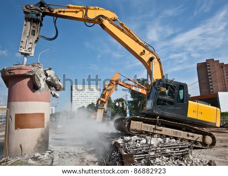 Hydraulic Crushing Hammer demolishing reinforced concrete structures - stock photo