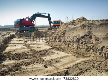 Hydraulic excavator and truck at work. - stock photo
