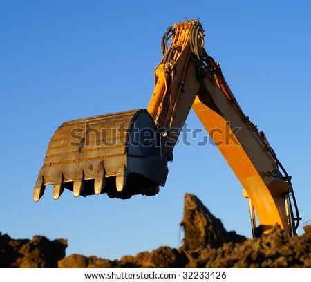 Hydraulic excavator at work. Shovel bucket against blue sky - stock photo