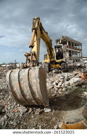 Hydraulic Excavator Removing Remains of Demolition at Construction Site Against Blue Sky - stock photo