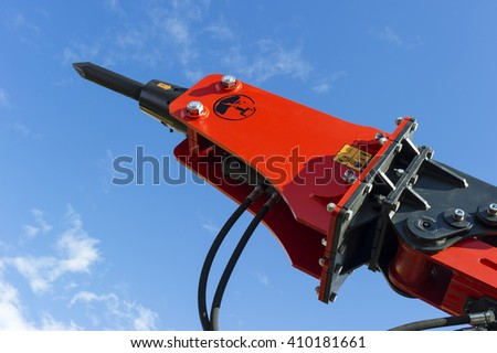 Hydraulic jackhammer for excavator, tractor, bulldozer and other construction machines, heavy industry, red demolition equipment, blue sky and white clouds on background  - stock photo