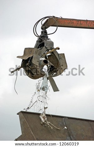 Hydraulic jaws on end of boom moving scrap metal - stock photo