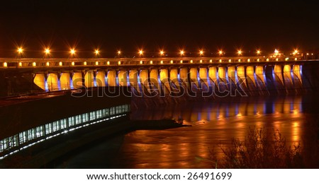 Hydroelectric dam in the night with road lights reflecting from the river - stock photo