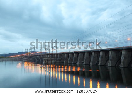 Hydroelectric power station at cloudy evening, posts with high-voltage wires. - stock photo