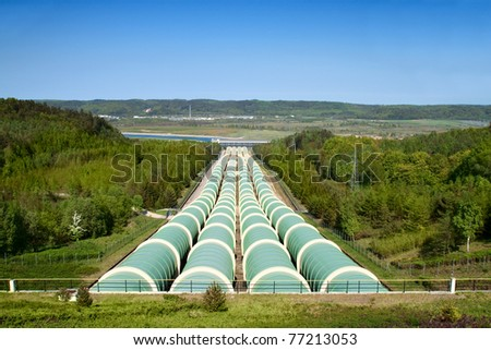 Hydroelectric power station with great water pipes. - stock photo