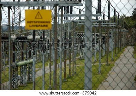 Hydropower transformation station with warning sign on fence - stock photo