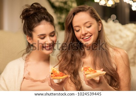 hygge, food and pajama party concept - happy female friends or teenage girls eating pizza at home