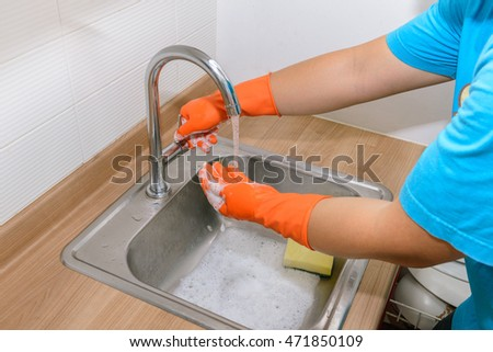 Hygiene. Cleaning Hands wearing gloves. Washing hands in the kitchen
