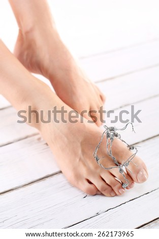 Hygiene feet, nail plastic.The rate of women wrapped in barbed wire, symbol of the pain of injury - stock photo