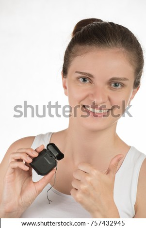 Hygiene of the oral cavity. Young girl cleans teeth with floss, smiling and showing okay sign on white background.