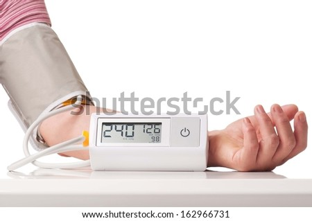 Hypertensive crisis fixed by electronic pressure measuring instrument over white background - stock photo