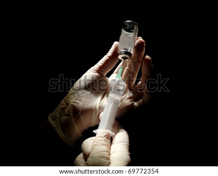 hypodermic syringe that is being filled with vaccine - stock photo