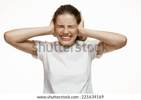 Hysteric girl covering her ears with hands. Don't hear. Don't want to hear / Gorgeous girl in plain white T-shirt. Mixed race Latina Caucasian young woman gesticulating isolated on white background  - stock photo