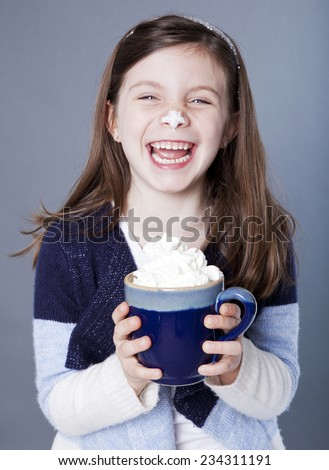 Hysterical little girl with a mug of hot cocoa and whipped cream on her nose - stock photo