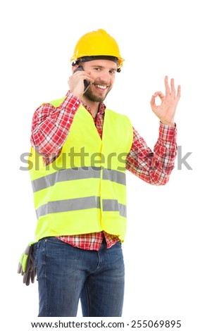 I agree. Smiling construction worker in yellow helmet and lime waistcoat talking on a phone and showing ok sign. Three quarter length studio shot isolated on white. - stock photo