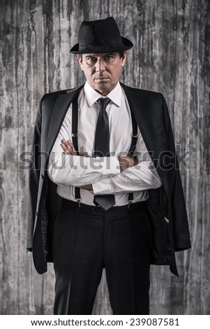I am a boss! Bossy senior man in gangster clothing keeping arms crossed and looking at camera while standing against a wall - stock photo