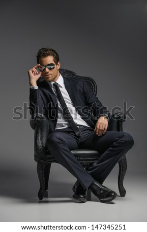 I am a boss. Confident young businessmen in sunglasses sitting on the vintage chair while isolated on grey - stock photo