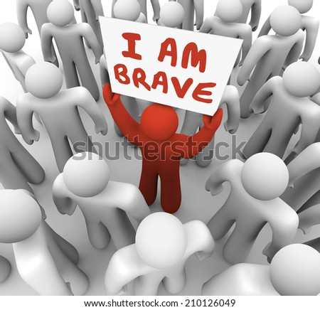 I Am Brave words on a sign held by one man in a crowd showing he is unique and different in being bold, daring, courageous and confident - stock photo