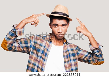 I am cool!  Handsome young Afro-American hipster pointing on his hat while standing against grey background - stock photo