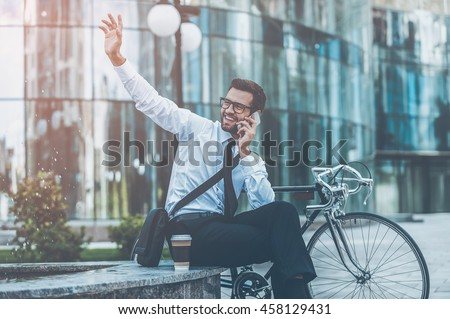I am here! Cheerful young businessman talking on the mobile phone and waving somebody while sitting near his bicycle with office building in the background - stock photo