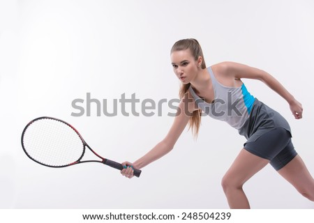 I am in game. Beautiful young woman in sports clothes holding tennis racket and looking  away while standing against white background - stock photo
