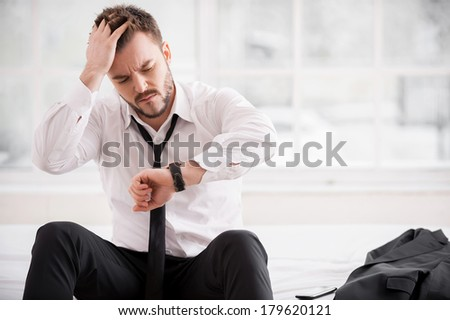I am late again! Frustrated young man in shirt and tie checking the time and holding hand in hair while sitting on the bed   - stock photo