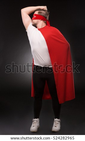 I am my own hero. Egoist or selfish super hero man posing isolated on grey background. Handsome man with red mask on kissing his biceps in studio.