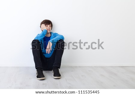 I am not in the mood today - bored teenager boy sitting by the wall - stock photo