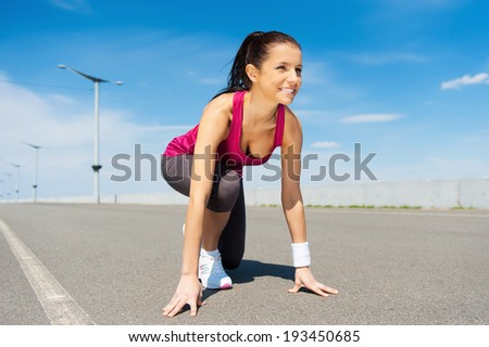 I am ready!  Beautiful woman in sports shoes standing in starting line and smiling - stock photo