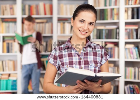 I am ready for my exam. Beautiful young woman holding a book and smiling while man reading on the background - stock photo