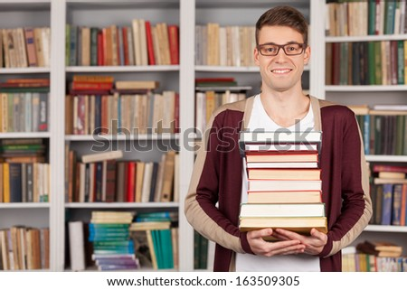 I am ready to my final exam. Cheerful young man holding a book stack and smiling while standing at the library - stock photo